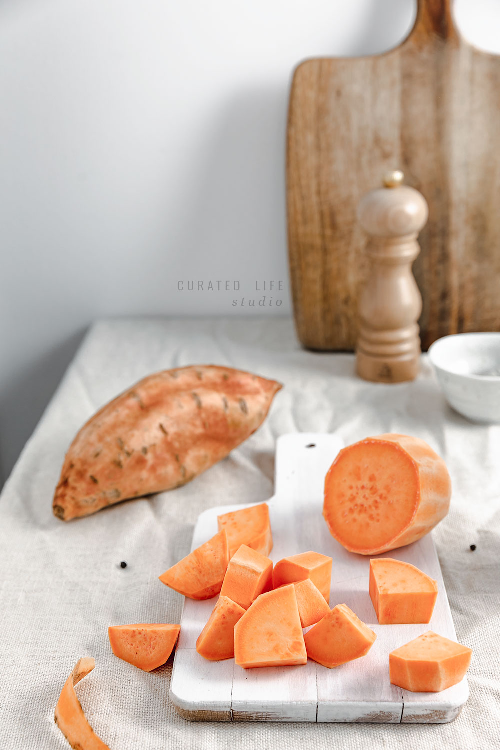 Front-view of cubed freshly chopped sweet potato sitting on a white chopping board. The spices and a lone pepper mill can be seen in the background.