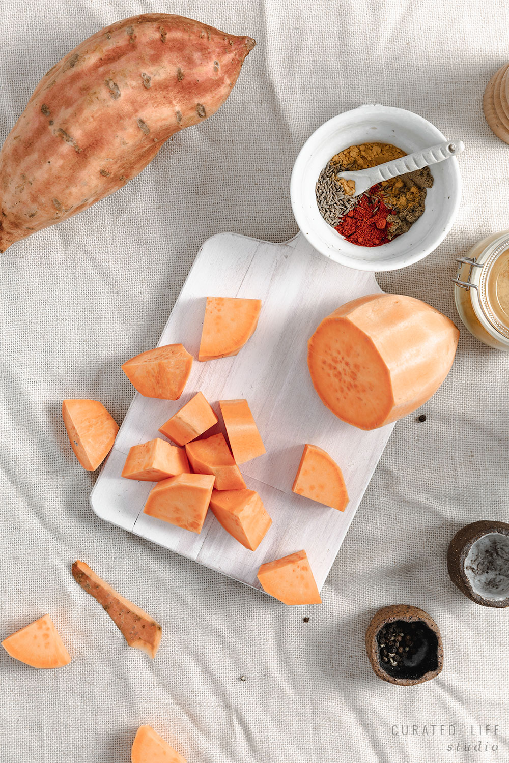 A bird's eye view of the chopped sweet potato. Herbs and a spoon share the white chopping board, suggestive that it will soon be sprinkled on the dish.