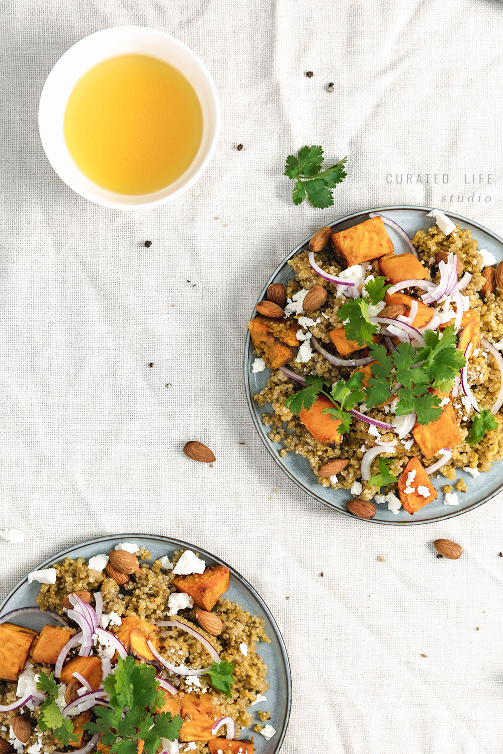 Birds Eye View of two plates of the Healthy Quinoa & Roasted Sweet Potato Salad and a gorgeous orange dressing.  #healthy #roasted #vegan #dressing #recipes #easy #quinoa