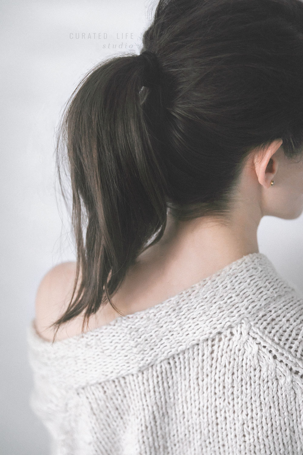 A girl faces a wall with a large woollen robe draped over her shoulder. Her hair is dark, brunette and tied messily in a ponytail. On a white wall beside her, faint lines of light paint the wall, reminiscent of the morning.