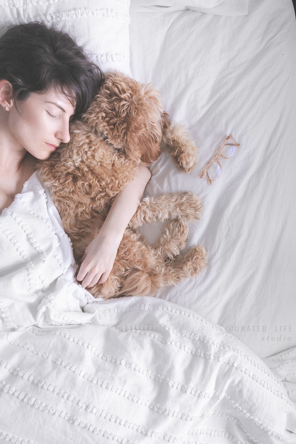 Birds-eye view of a brunette woman sleeping, cuddling a tan caboodle in bed, surrounded by white linen bedsheets,