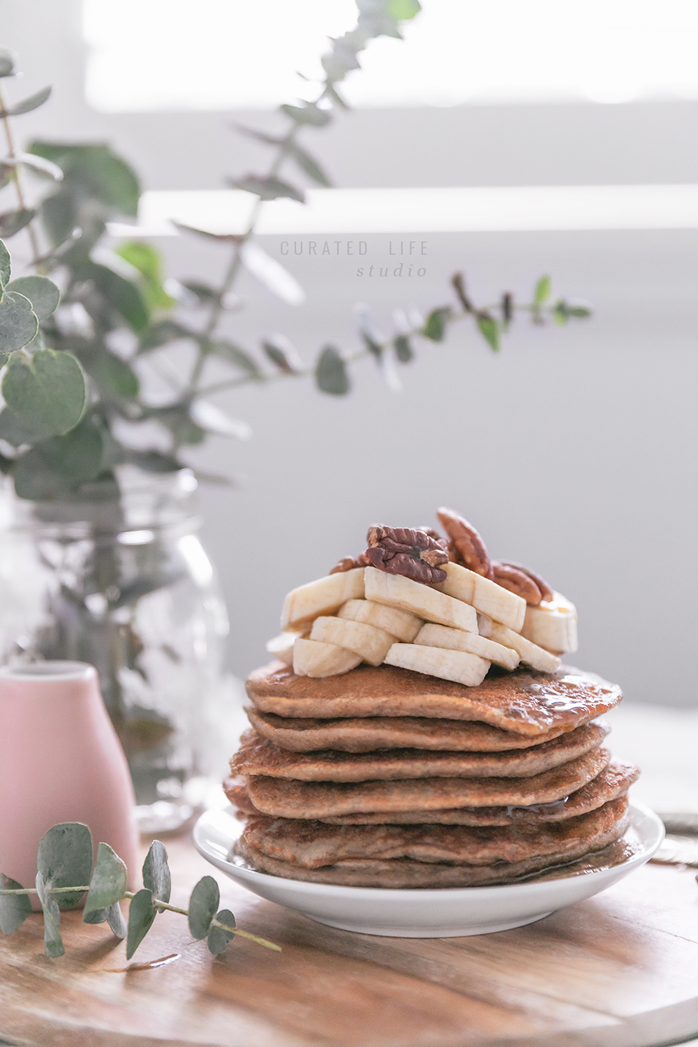 A macro image of the stack of banana pancakes. In the foreground sits a jar spilling with eucalyptus leaves and a small pink ceramic jar filled with maple syrup.
