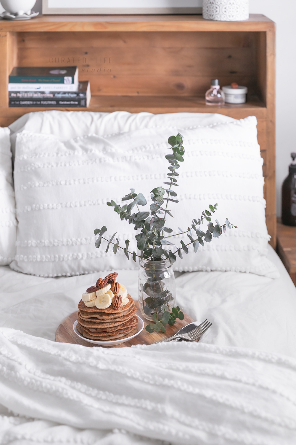 A large wooden rustic bed with shelves with a careful selection of books and perfume. In the middle of the bed is a round wooden tray filled with a stack of gluten-free banana pancakes, silver antique cutlery and a fresh bouquet of eucalyptus leaves.