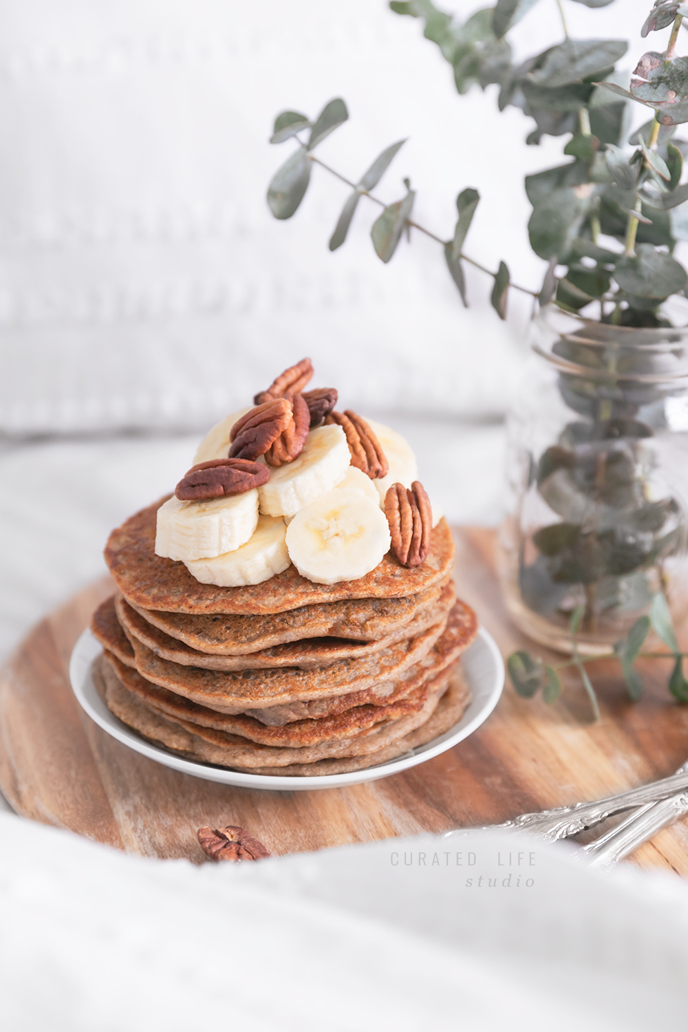 A stack of banana pancakes presented on a rustic wooden tray beside antique silver cutlery.