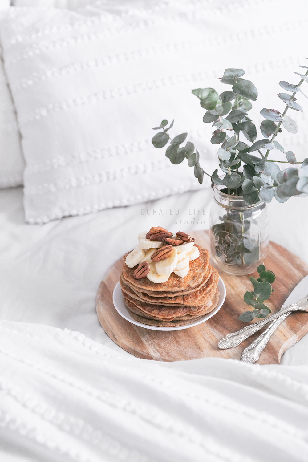 Looking down on a bed draped in white linen, and a stack of fluffy banana pancakes sitting on a rustic wooden tray, beside a jar of eucalyptus leaves.