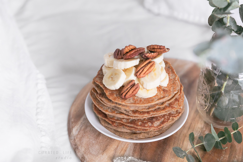 Peering through the eucalyptus foliage, a stack of banana pancakes presented on a rustic wooden tray beside antique silver cutlery.