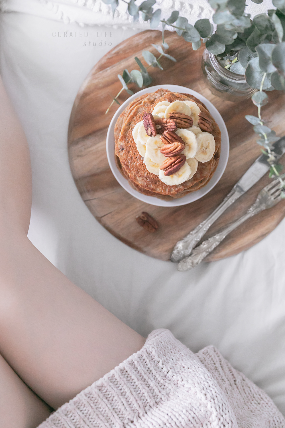 Birds-eye view of a woman sitting on the bed beside the wooden tray filled with banana pancakes, overflowing in fresh banana and toasted pecans.