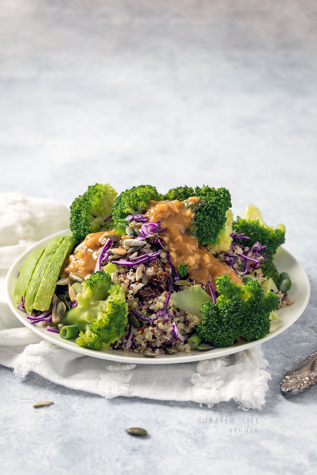 The pale blue background, white linen napkins and light-filled table are reminiscent of summer. In front of you sits a plate of a fresh Broccoli Salad with a drizzle of Peanut Dressing. Sunflower seeds scatter the table.