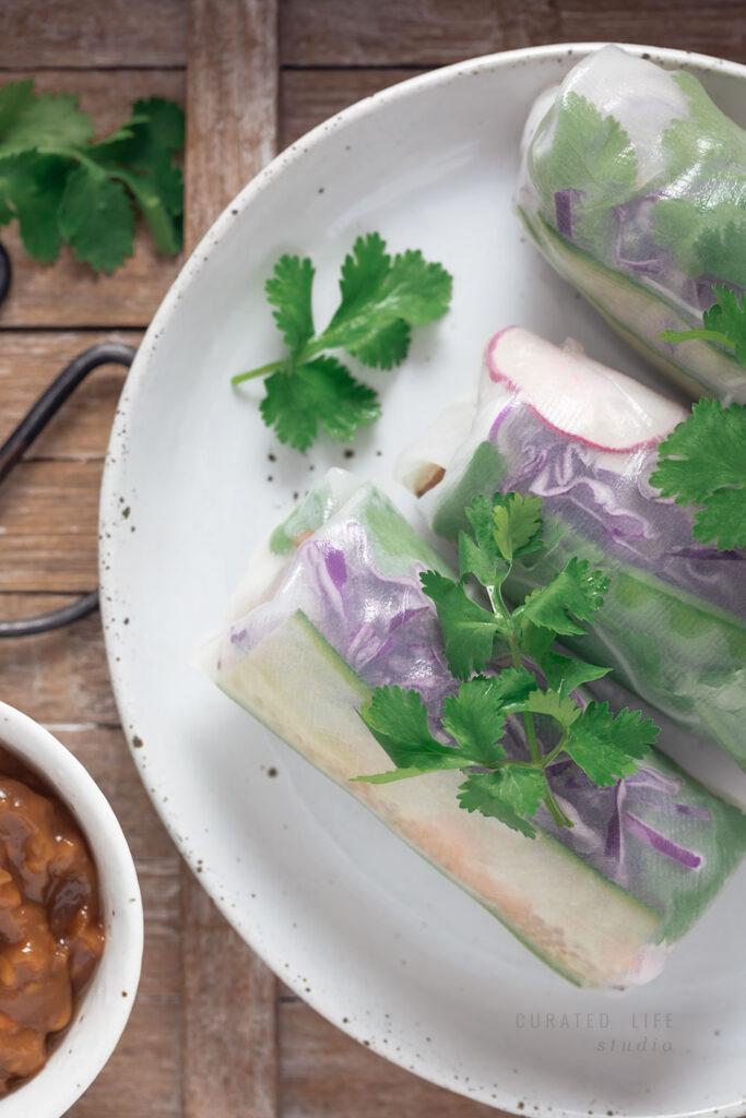Macro wooden tray where a plate of Fresh Rice Paper Rolls sit.  #Vietnamese #Healthy #Peanut #Dipping #Sauce #Vegetarian #Vegan #Gluten-free #Tofu #Recipe #Rice #Paper #Spring #Rolls #Fresh