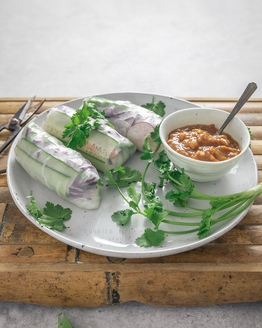 On a yellow bamboo tray sits some  Vietnamese Fresh Spring Rolls with Peanut Dipping Sauce, everything blanketed in sprigs of cilantro.   #Vietnamese #Healthy #Peanut #Dipping #Sauce #Vegetarian #Vegan #Gluten-free #Tofu #Recipe #Rice #Paper #Spring #Rolls #Fresh